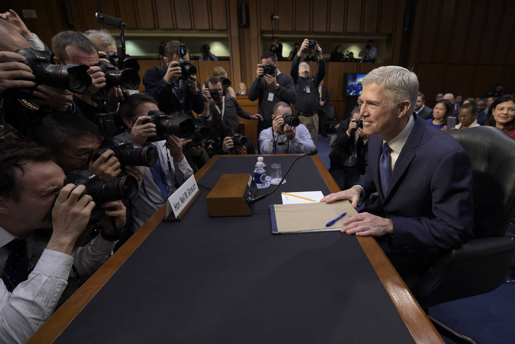 Supreme Court Justice nominee Neil Gorsuch is surrounded by photographers as he arrives on Capitol Hill in Washington, Monday, March 20, 2017, for his confirmation hearing before the Senate Judici ...