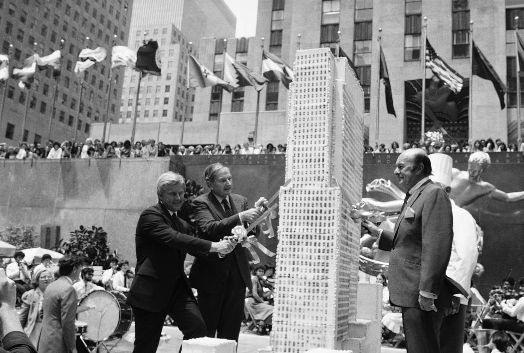 David Rockefeller, second left, Rockefeller Center chairman and Center President Richard H. Voell, left, and New York City Board of Education President Joseph Barker, right, begin to slice up an e ...