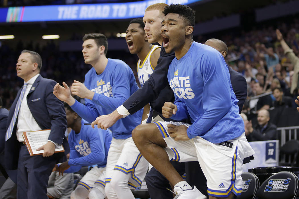 Members of the UCLA basketball team celebrate after the Bruins scored against Cincinnati during the second half of a second-round game of the NCAA men's college basketball tournament in Sacramento ...