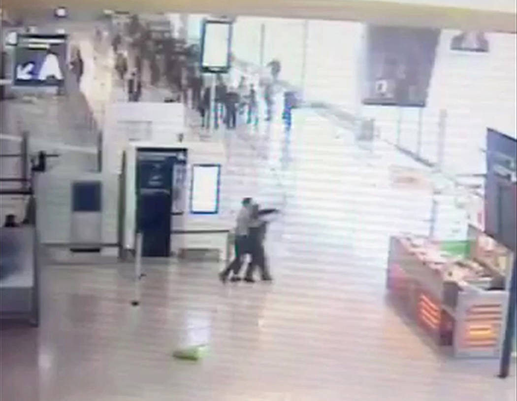 In this image taken from video of CCTV footage provided to AP on the condition that its source not be revealed, suspected Islamic extremist Ziyed Ben Belgacem, center left, holds a soldier after g ...