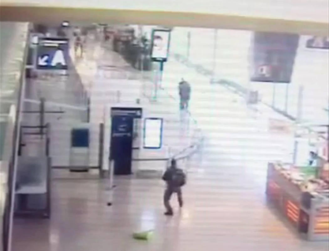 In this image taken from video of CCTV footage provided to AP on the condition that its source not be revealed, suspected Islamic extremist Ziyed Ben Belgacem, center top, holds a soldier after gr ...