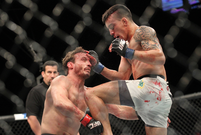 Thomas Almeida, right, uses a flying knee to knockout Brad Pickett during UFC 189 at the MGM Grand Garden Arena Saturday, July 11, 2015, in Las Vegas. (Chase Stevens/Las Vegas Review-Journal) Foll ...