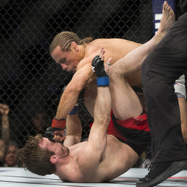 Urijah Faber, right, punches Brad Pickett in the UFC Fight Night bantamweight bout at the Golden 1 Center on Saturday, Dec. 17, 2016, in Sacramento, Calif. Faber won by unanimous decision. Erik Ve ...
