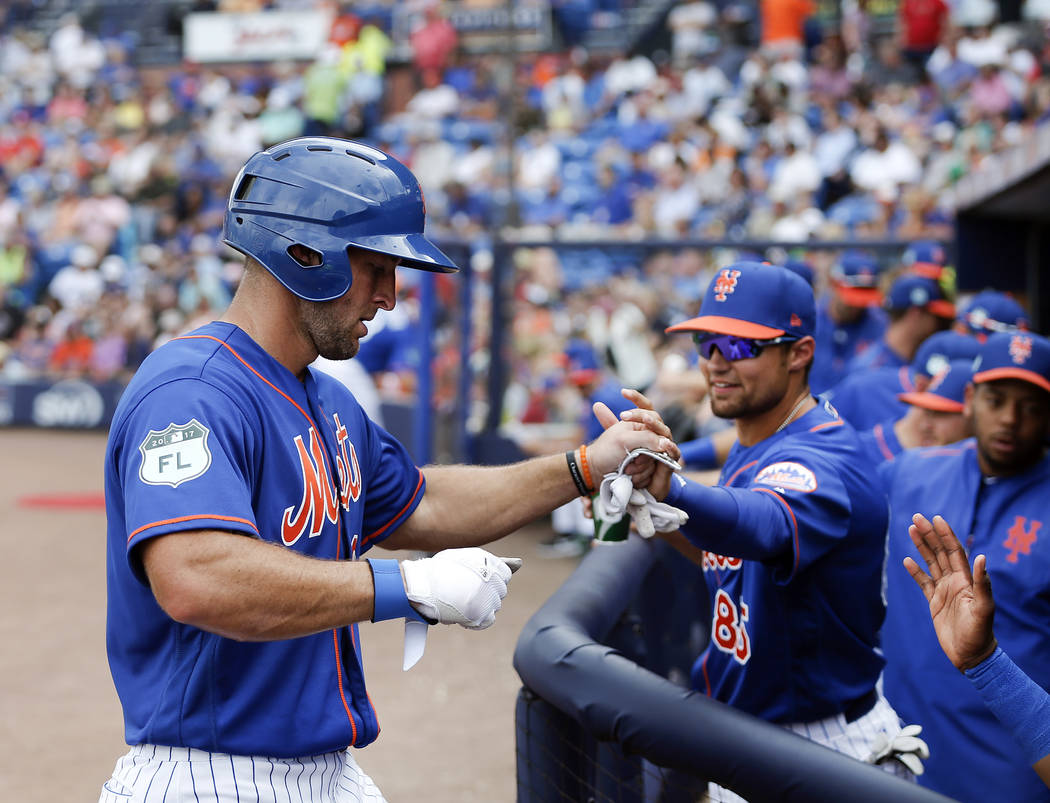 New York Mets' Tim Tebow, left, is greeted as he returns to the dugout after his first hit of spring training in the fifth inning of a spring training baseball game against the Miami Marlins Monda ...