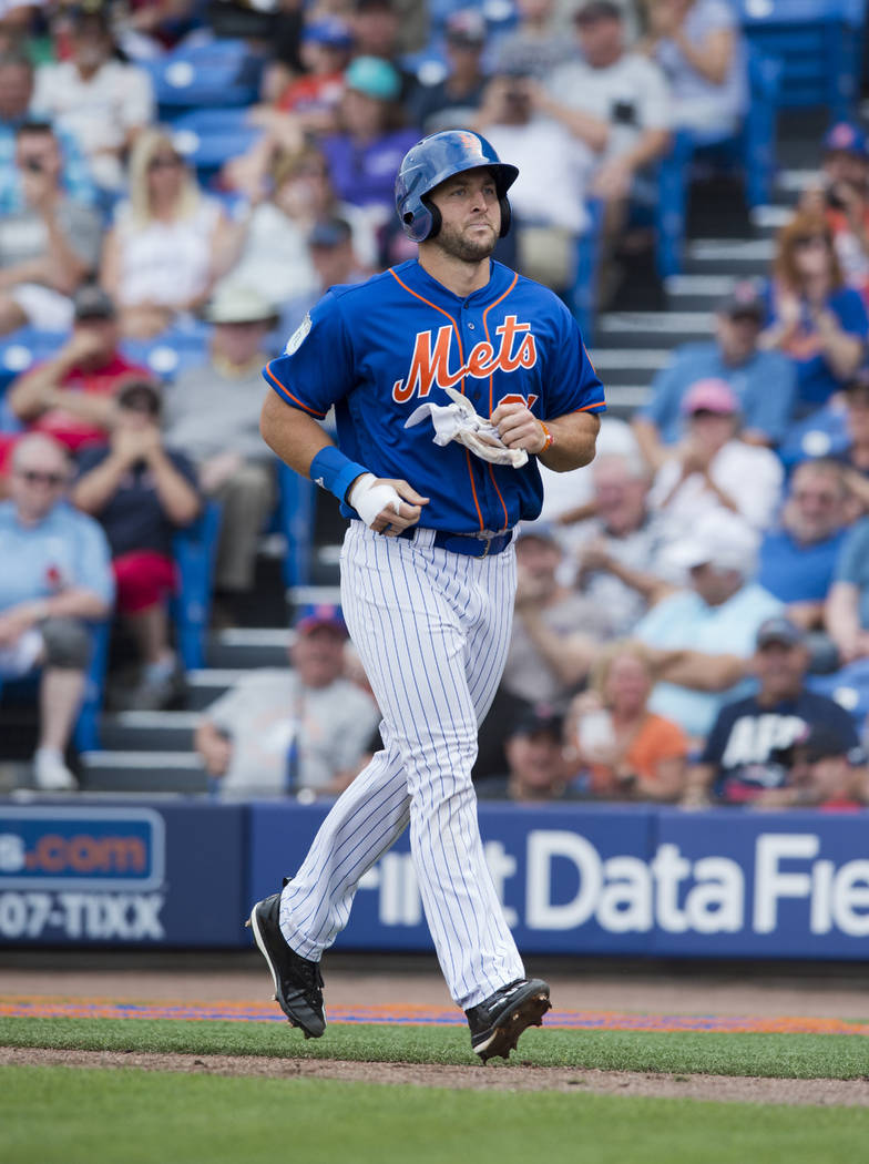 New York Mets designated hitter Tim Tebow makes his way back to the dugout in the fourth inning after he grounded into a double play during a spring training baseball game against the Boston Red S ...