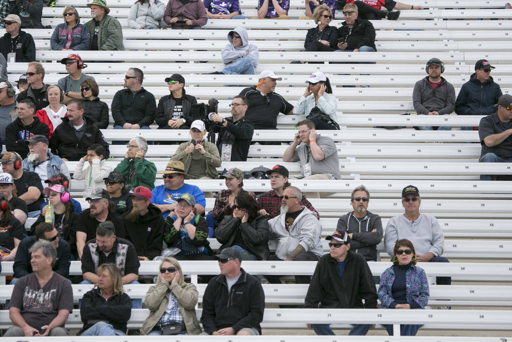 Fans cover their ears while they watch National Hot Rod Association drivers race in a qualifying session at The Strip at Las Vegas Motor Speedway on Friday, March 31, 2017, in Las Vegas. (Bridget  ...