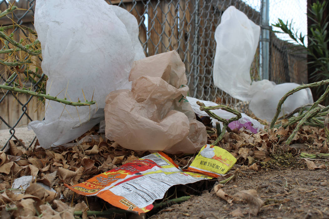 Plastic bags and other garbage line a fence across the  street from the Nevada Division of Parole and Probation building in Las Vegas, Tuesday, March 21, 2017. If Assembly Bill 344 is passed, it w ...