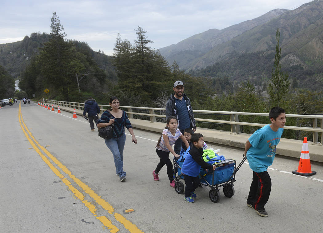In this Feb. 13, 2017, file photo, Maria Placencia and her husband Jesus Mora follow their children as they pull a wagon full of groceries across the storm damaged Highway 1 Pfeiffer Canyon Bridge ...