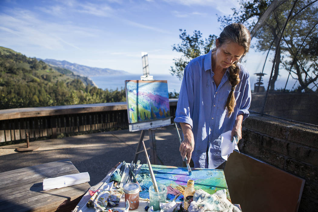 In this March 8, 2017, photo, Nepenthe resident artist Erin Gafill paints the coastline while the restaurant is closed due to damage from the recent storms in Big Sur, Calif. Residents are adjusti ...