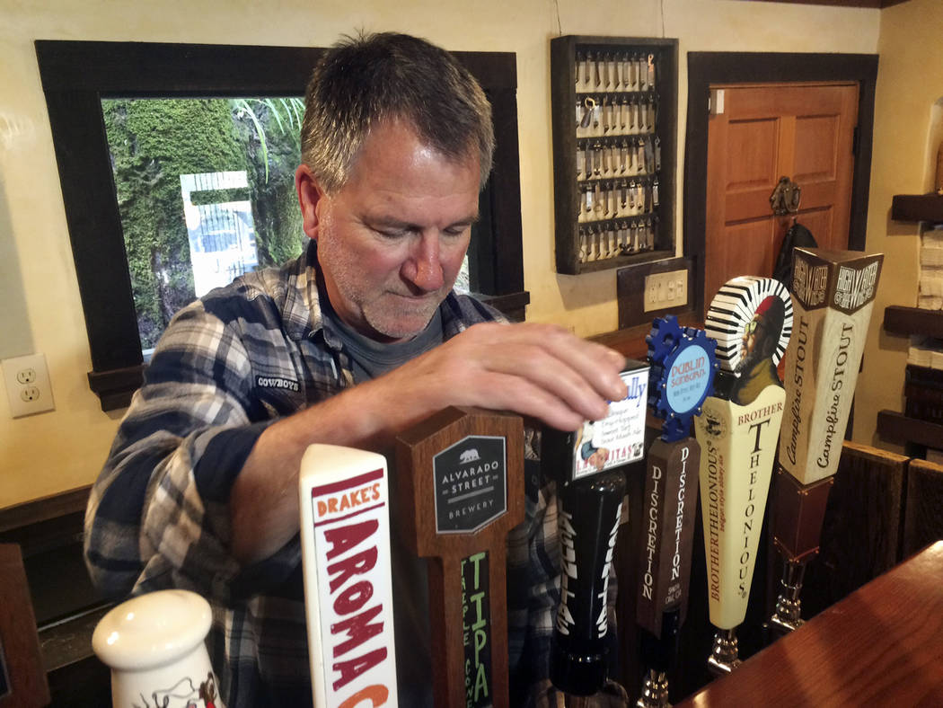 In this March 16, 2017, photo, Big Sur Taproom and Deli owner Kurt Mayer pours a beer in Big Sur, Calif. The tap room and deli are the only businesses open in town on the south side of the bridge  ...
