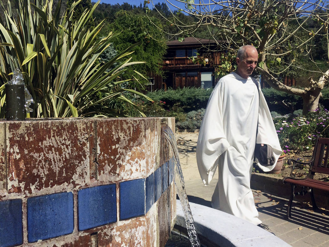 In this March 16, 2017, photo, Father Cyprian Consiglio walks the grounds at the New Camaldoli Hermitage in Big Sur, Calif. Residents are adjusting after a bridge on the Central California coast c ...