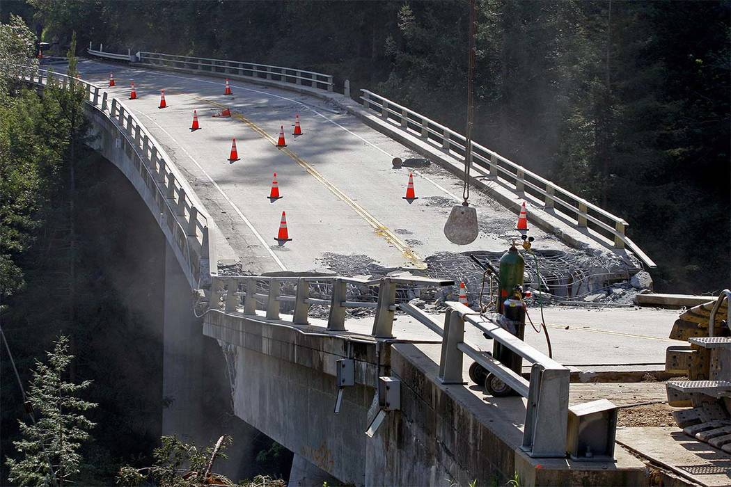 Crews use a wrecking ball attached to a crane on the demolition of the storm-damaged Pfeiffer Canyon Bridge in Big Sur, California. The crumbling bridge along the California coast has stranded res ...