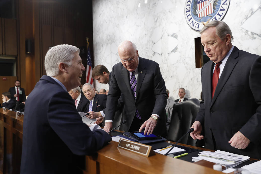 Supreme Court Justice nominee Neil Gorsuch talks with Senate Judiciary Committee members Sen. Richard Durbin, D-Ill., right, and Sen. Patrick Leahy, D-Vt. on Capitol Hill in Washington, Tuesday, M ...