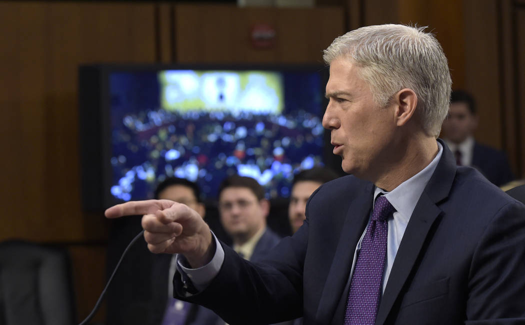 Supreme Court Justice nominee Neil Gorsuch points to a photographer as arrives on Capitol Hill in Washington, Tuesday, March 21, 2017, for his confirmation hearing before the Senate Judiciary Comm ...