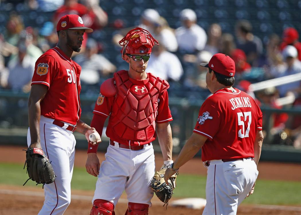 Cincinnati Reds pitching coach Mack Jenkins (57) comes out to talk with starting pitcher Amir Garrett (50) and catcher Rob Brantly, middle, during the second inning of a spring training baseball g ...