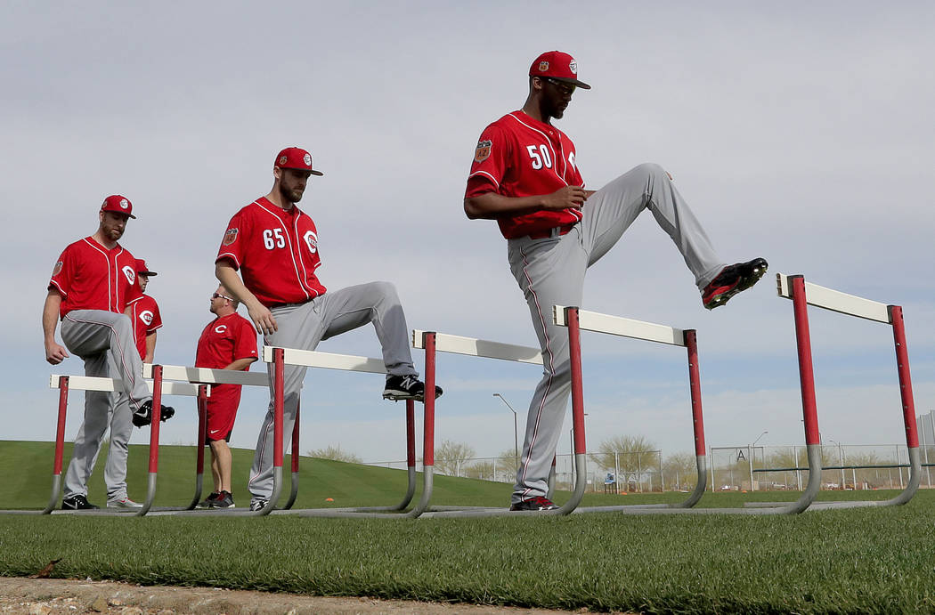 Cincinnati Reds' Amir Garrett (50) and Lucas Luetge (65) workout on an obstacle course during the teams' first day of spring training baseball workouts, Tuesday, Feb. 14, 2017 in Goodyear, Ariz.   ...