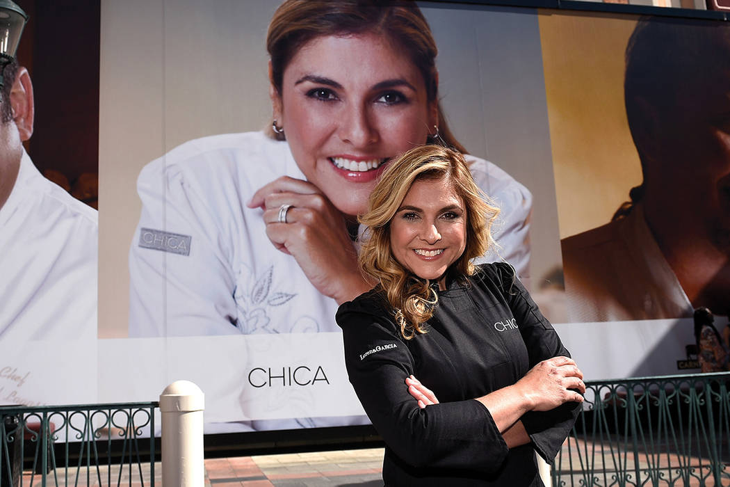 Chef Lorena Garcia poses by a 21-foot-tall poster of herself after its debut on the wall of chefs at the Venetian Las Vegas Wednesday, Feb. 15, 2017, in Las Vegas. (David Becker/Las Vegas News Bureau)