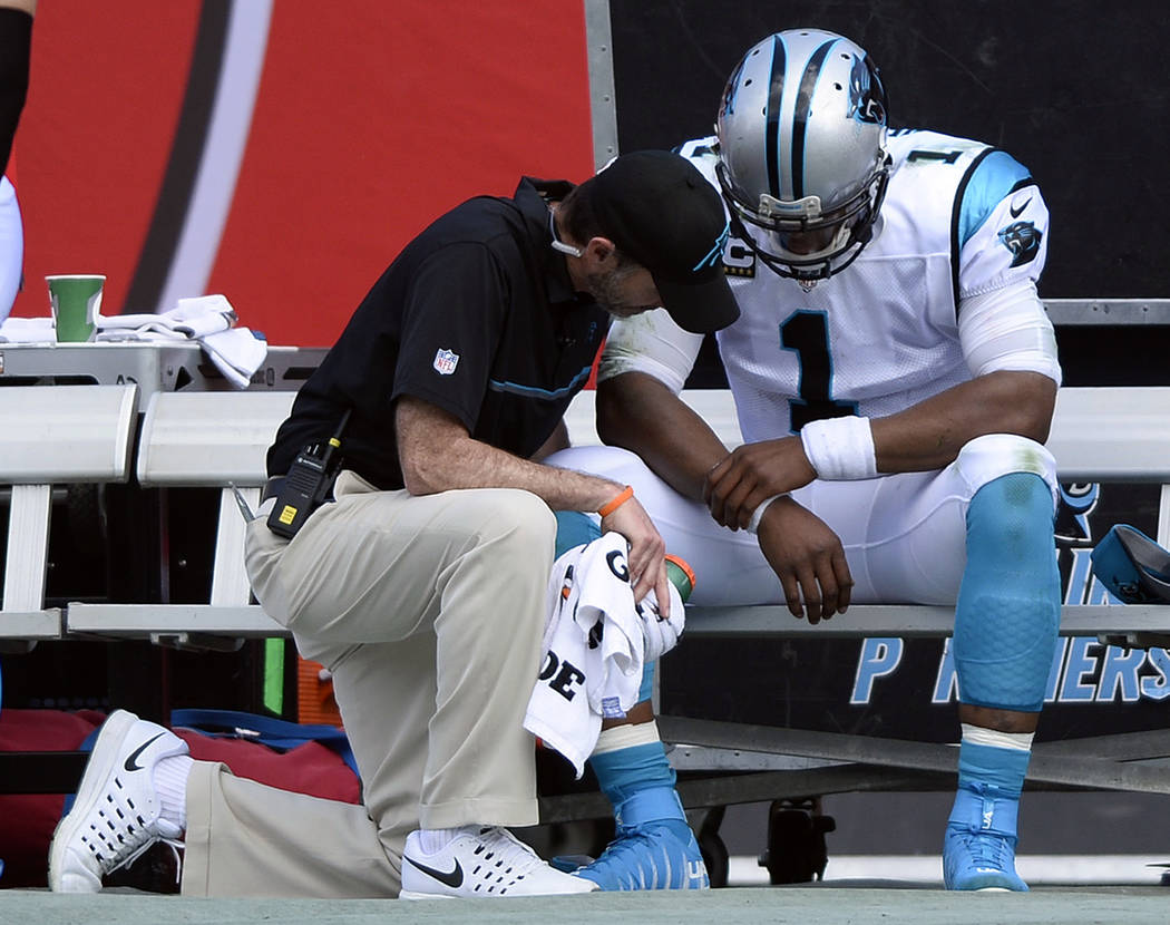 In this Jan. 1, 2017, file photo, a trainer looks at Carolina Panthers quarterback Cam Newton (1) during the second quarter of an NFL football game against the Tampa Bay Buccaneers in Tampa, Fla.  ...