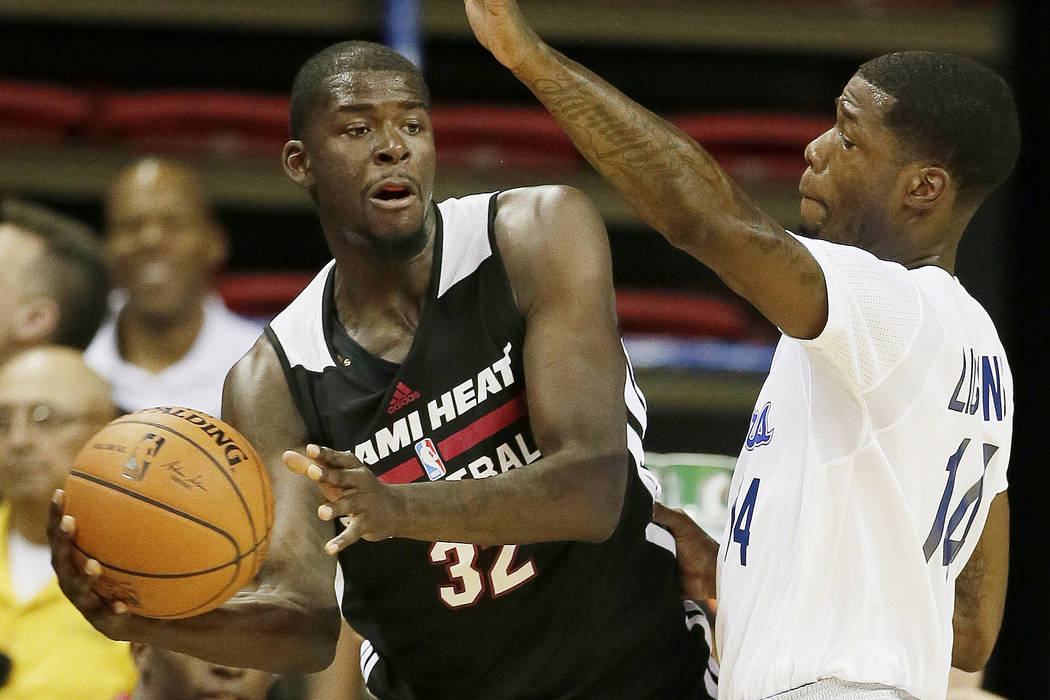 Las Angeles Clippers' DeAndre Liggins, right, guards against the Miami Heat's James Ennis during the first half of an NBA summer league basketball game Monday, July 14, 2014, in Las Vegas. (AP Pho ...