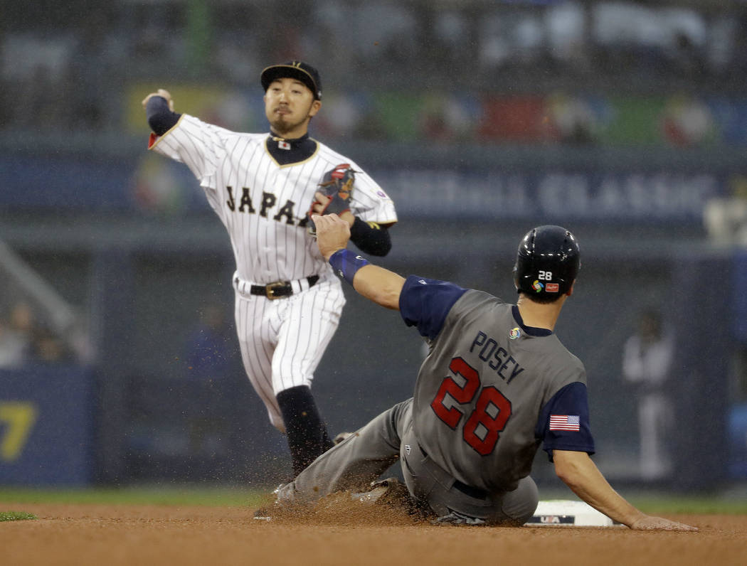United States' Buster Posey is safe at second as Japan's Ryosuke Kikuchi throws to first during the third inning of a semifinal in the World Baseball Classic in Los Angeles, Tuesday, March 21, 201 ...