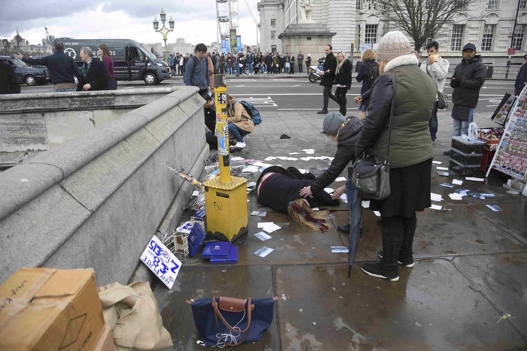 A woman lies injured after a shottingt incident on Westminster Bridge in London, March 22, 2017. (Toby Melville/Reuters)
