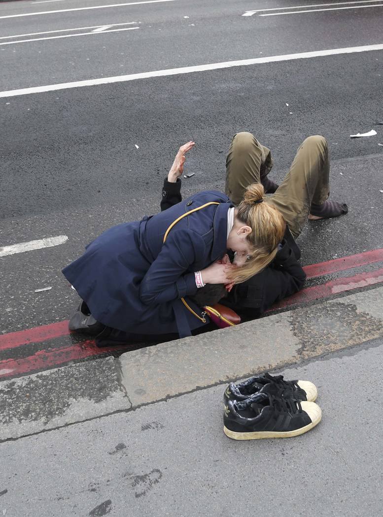 An injured person is assisted after an incident on Westminster Bridge in London, Britain March 22, 2017.  REUTERS/Toby Melville