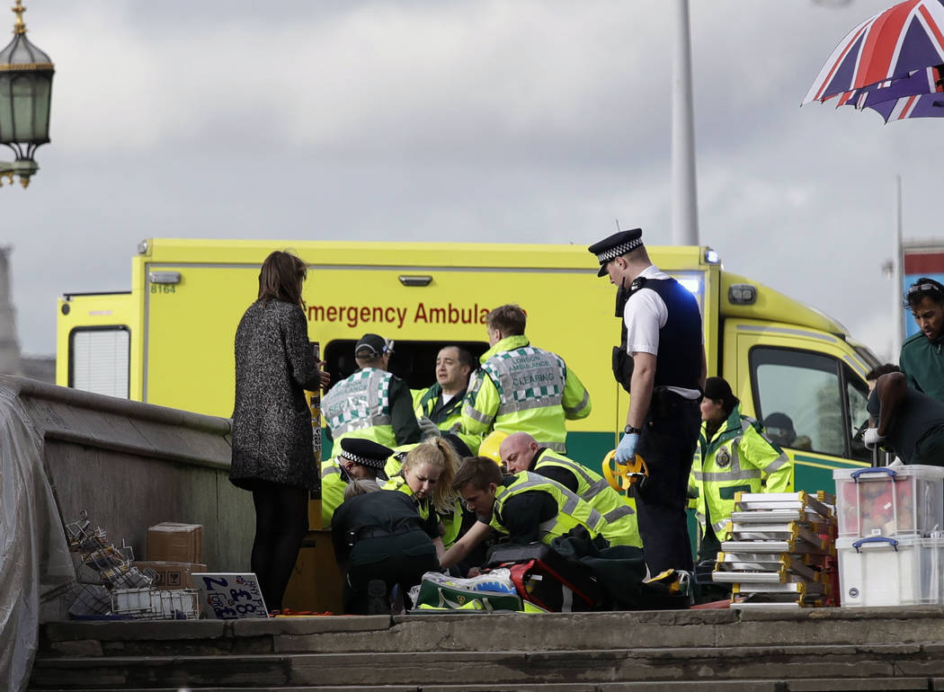 Emergency services staff provide medical attention close to the Houses of Parliament in London, Wednesday, March 22, 2017. London police say they are treating a gun and knife incident at Britain's ...