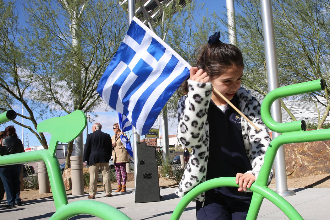 Anastasia Georgiadis, 7, plays while holding the flag of Greece prior to the start of the Greek Independence Day with a flag raising ceremony outside the City Hall on Thursday, March 23, 2017, in  ...