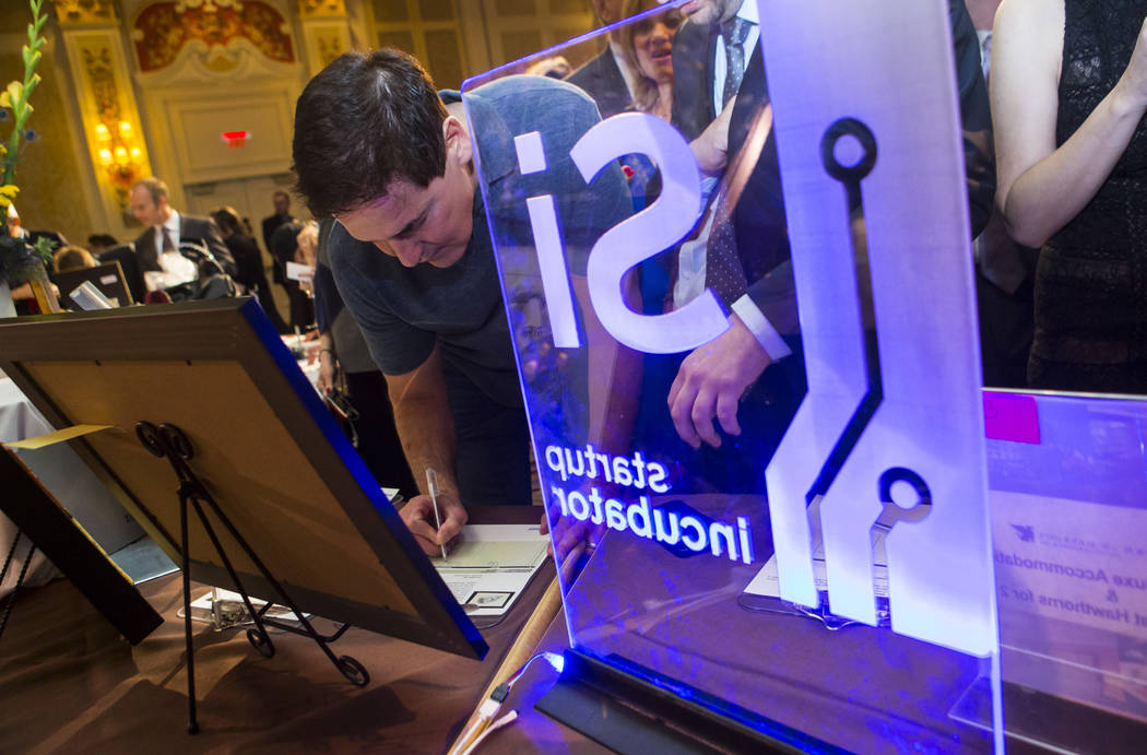 Entrepreneur Mark Cuban, left, places a bid at the silent auction during the Adelson Educational Campus' 13th annual In Pursuit of Excellence Gala at The Venetian hotel-casino in Las Vegas on Sund ...