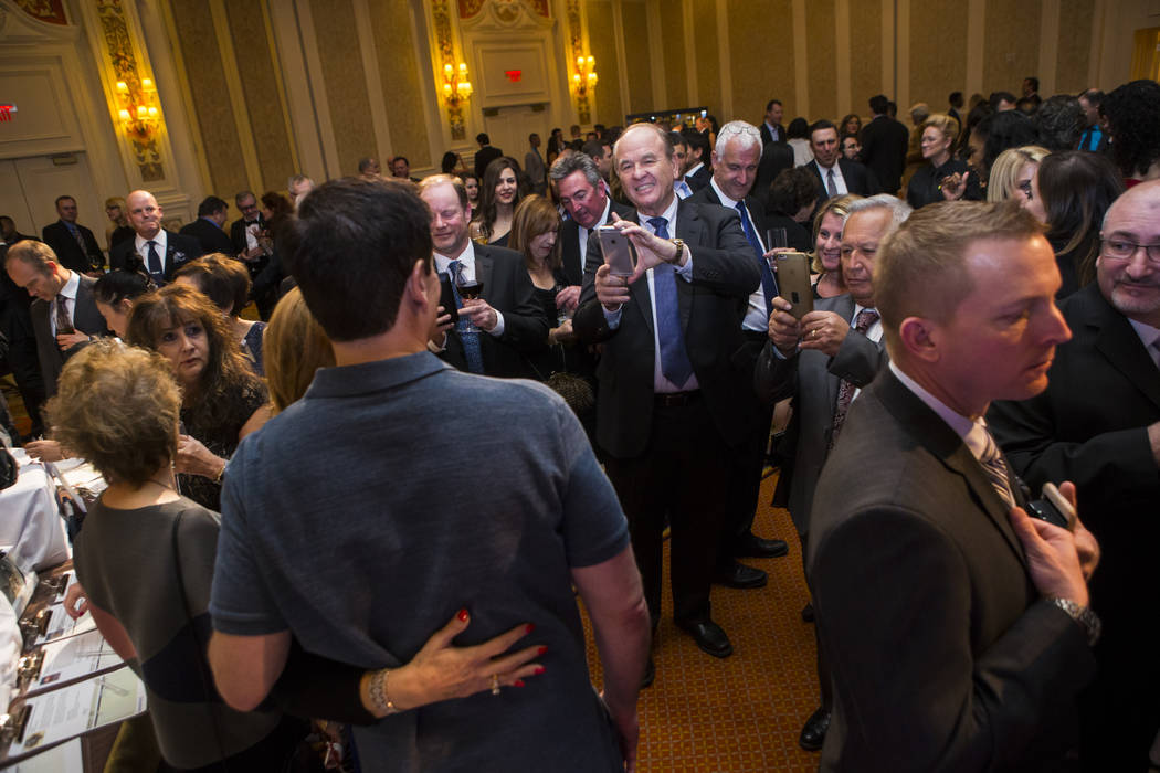 Attendees take photos with entrepreneur Mark Cuban during the Adelson Educational Campus' 13th annual In Pursuit of Excellence Gala at The Venetian hotel-casino in Las Vegas on Sunday, March 26, 2 ...