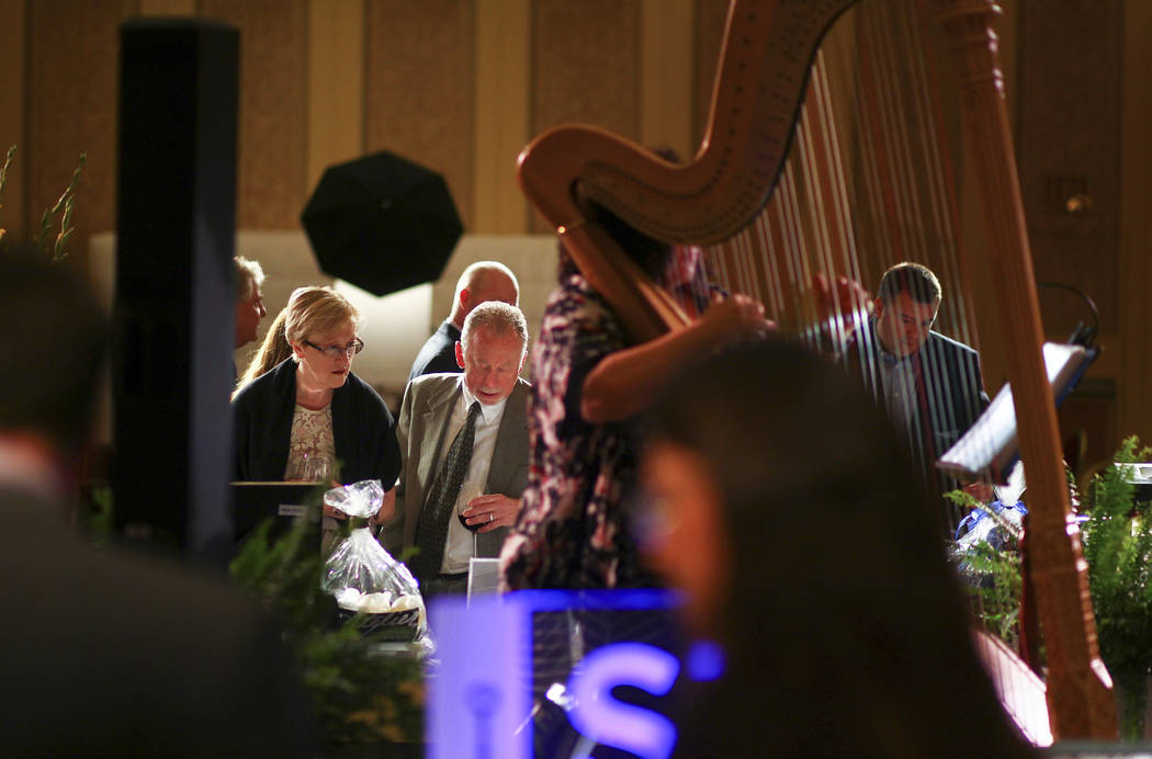 Attendees look through silent auction items during the Adelson Educational Campus' 13th annual In Pursuit of Excellence Gala at The Venetian hotel-casino in Las Vegas on Sunday, March 26, 2017. (C ...