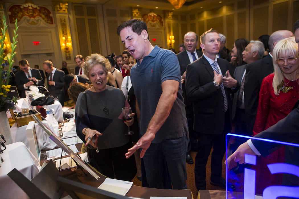 Entrepreneur Mark Cuban, center, looks at silent auction items with an attendee during the Adelson Educational Campus' 13th annual In Pursuit of Excellence Gala at The Venetian hotel-casino in Las ...