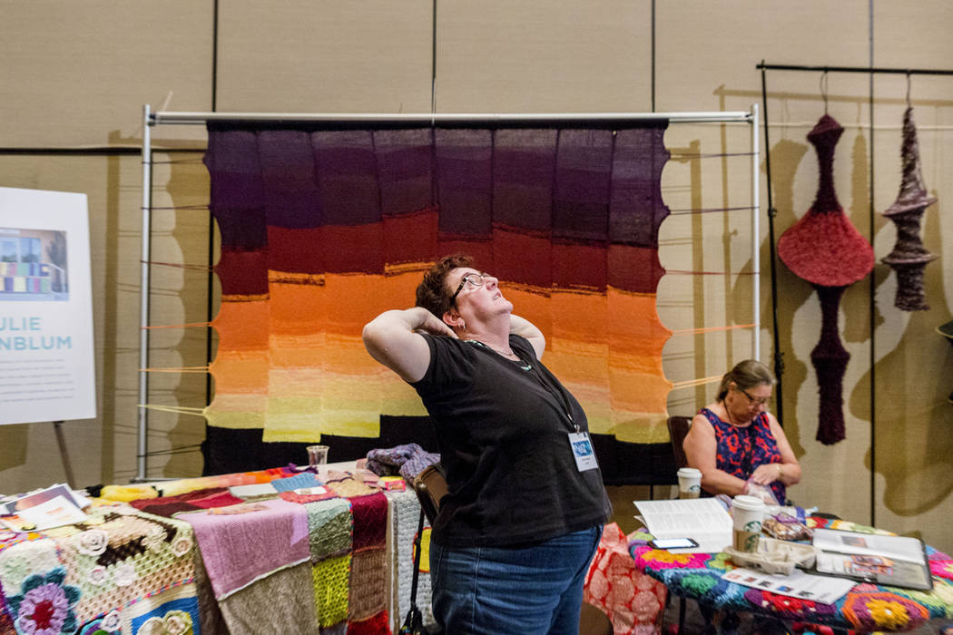 Julie Kornblum, an artist with Yarn Bombing Los Angeles, partakes in a yoga session at her booth during Vogue Knitting Live held at the Red Rock Resort in Las Vegas, Sunday, March 25, 2017. (Eliza ...