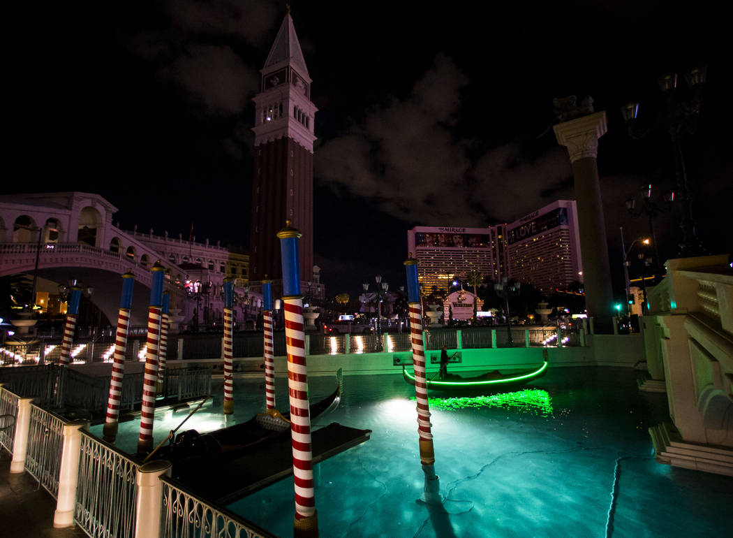 A gondolier passes by as the Venetian hotel-casino commemorates Earth Hour by turning off exterior lighting, rooftop signage and facade features for one hour in Las Vegas on Saturday, March 25, 20 ...