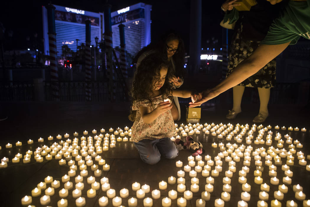 "Miriam Avalos, right, hands candles to her granddaughter, Elayne Favila, 4, as they work on a ""mural"" depicting Earth using LED tea lights to commemorate Earth Hour at the Venetian hotel-casino in ..."