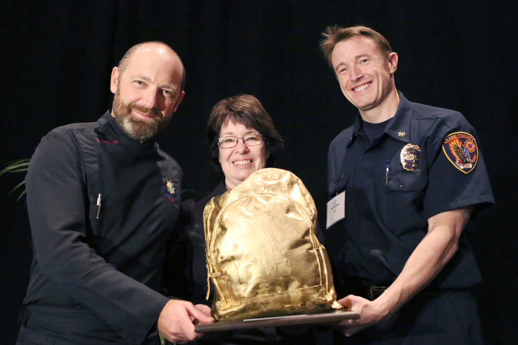 Chef Steve Benjamin, left, Commissioner, Mary Beth Scow, and Clark County Fire Deputy Chief, John Steinbeck, hold their 24-Karat gold painted backpack after winning the third annual Emergency Prep ...