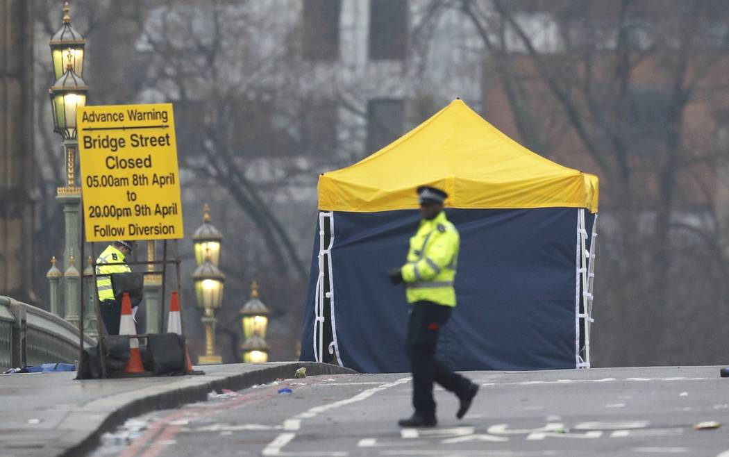 A police officer walks accross Westminster Bridge the morning after an attack by a man driving a car and wielding a knife left three dead and dozens injured, in London, Britain, March 23, 2017. (D ...