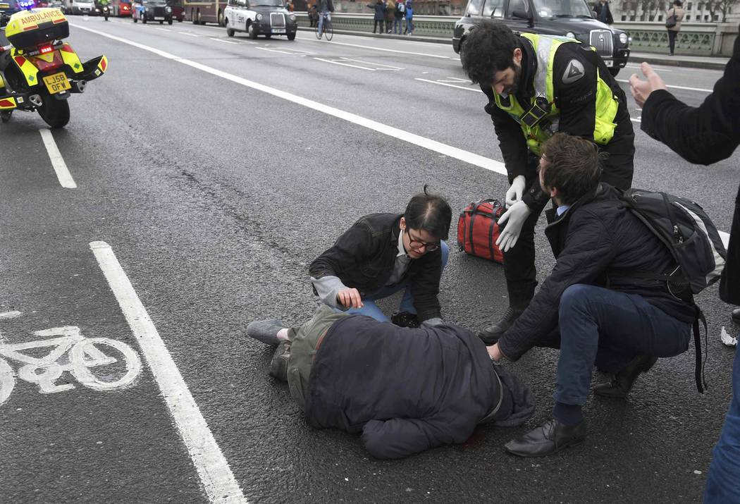 An injured person is assisted after on Westminster Bridge after a man drove his car intentionally into pedestrians and other cars on Wednesday, March 22, 2017. (Toby Melville/Reuters)