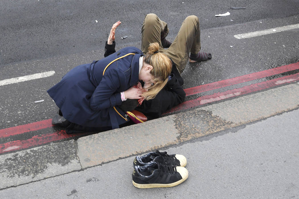 A woman assists an injured person on Westminster Bridge after a man drove his car intentionally into pedestrians and other cars on Wednesday, March 22, 2017. (Toby Melville/Reuters)