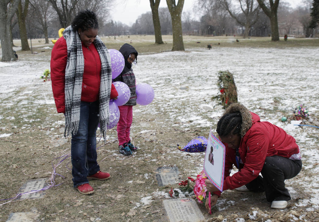In this Jan. 27, 2017, Helen Jackson, left, along with her daughter Raniah Ricks, center, and Brittany Blake visit the grave of Jackson's daughter Cataleya Tamekia-Damiah Wimberly. Wimberly died a ...