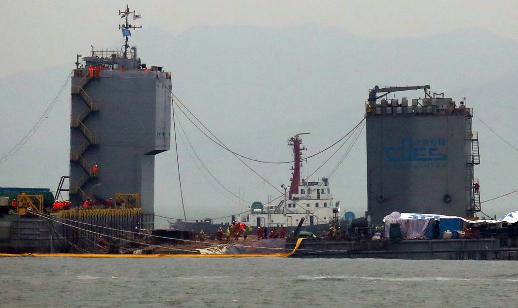 Workers prepare to lift the sunken Sewol ferry in waters off Jindo, South Korea, Thursday, March 23, 2017. South Korean workers on Thursday slowly pulled up a 6,800-ton ferry from the water, nearl ...