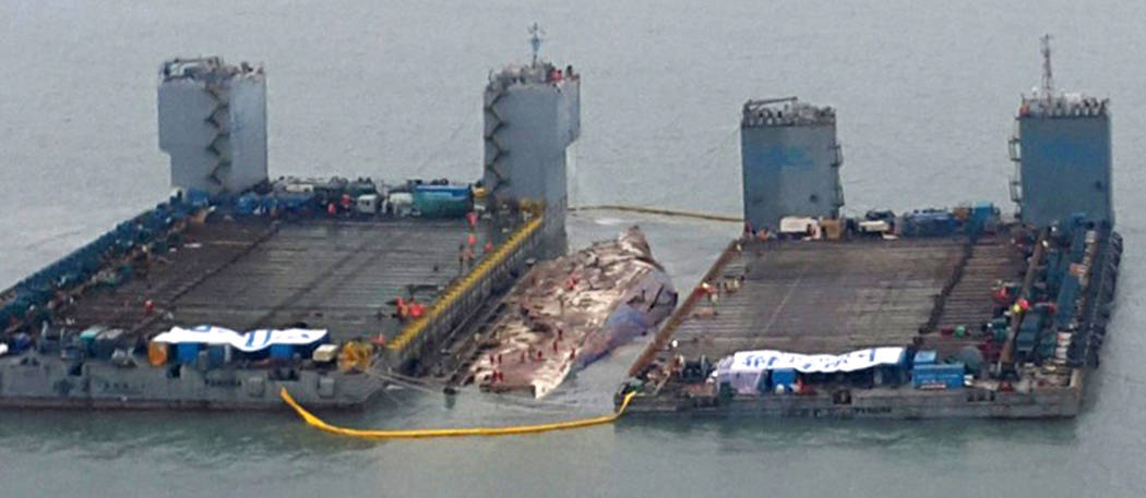In this photo provided by West Regional Headquarters Korea Coast Guard, workers prepare to lift the sunken Sewol ferry, center, in waters off Jindo, South Korea, Thursday, March 23, 2017. A 6,800- ...