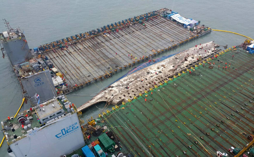 In this photo provided by West Regional Headquarters Korea Coast Guard, workers prepare to lift the sunken Sewol ferry, center, in waters off Jindo, South Korea, Thursday, March 23, 2017. (West Re ...