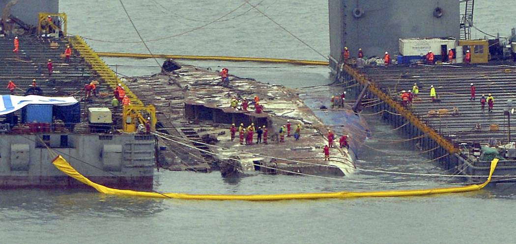 Workers prepare to lift the sunken Sewol ferry, center, in waters off Jindo, South Korea, Thursday, March 23, 2017. A 6,800-ton South Korean ferry emerged from the water on Thursday, nearly three  ...