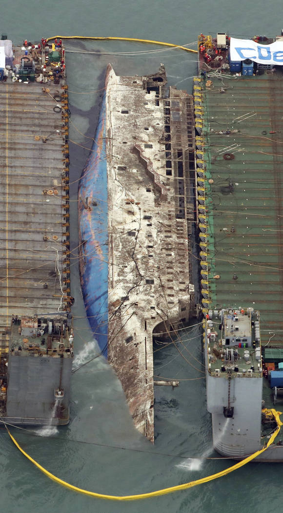 Workers try to raise the sunken Sewol ferry, center, between two barges during the salvage operation in waters off Jindo, South Korea, Thursday, March 23, 2017. (Choi Young-su/Yonhap via AP)