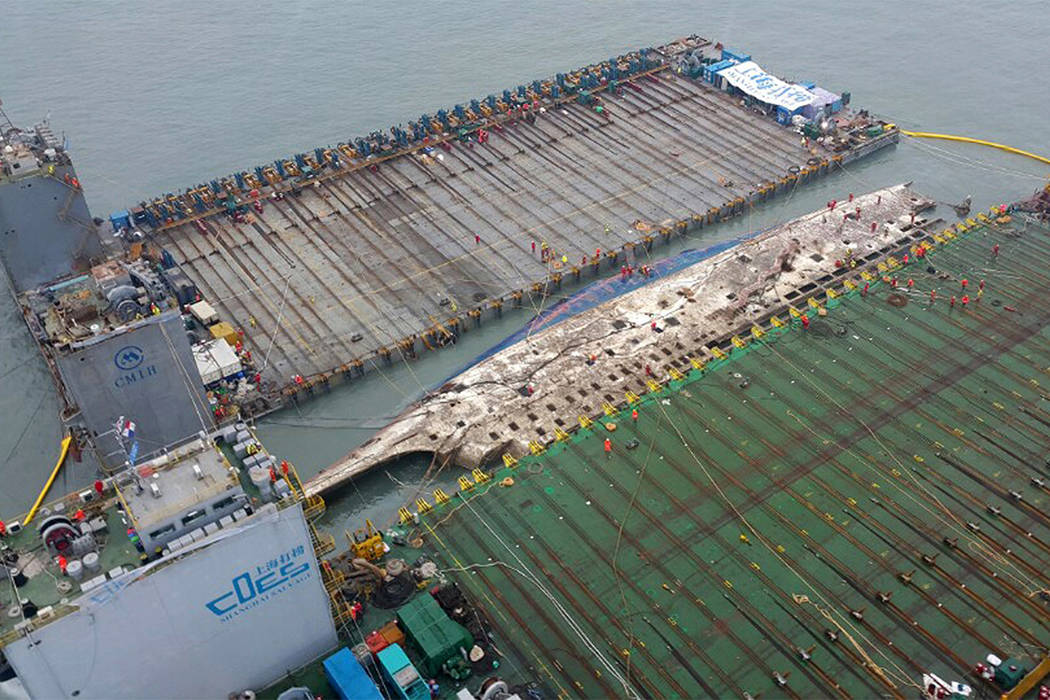 Workers prepare to lift the sunken Sewol ferry in waters off Jindo, South Korea, Thursday, March 23, 2017. A 6,800-ton South Korean ferry emerged from the water on Thursday, nearly three years aft ...