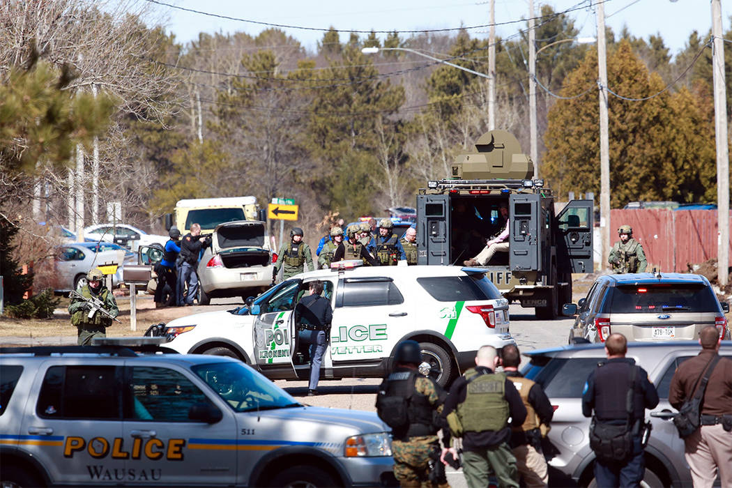 Numerous law enforcement vehicles and SWAT teams respond to a shooting Wednesday, March 22, 2017, at an apartment complex in Rothschild, Wisconsin. A police officer was among four who were killed. ...