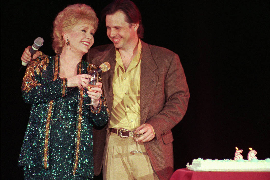 In this April 1, 1997, file photo, Debbie Reynolds, left, celebrates her 65th birthday on stage with her son, Todd Fisher. (Lennox McLendon/AP)