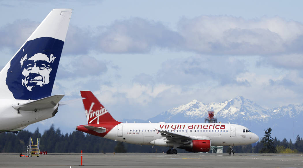 A Virgin America plane taxis past an Alaska Airlines plane waiting at a gate Monday, April 4, 2016, at Seattle-Tacoma International Airport in Seattle. Alaska said Wednesday, March 22, 2017, that  ...