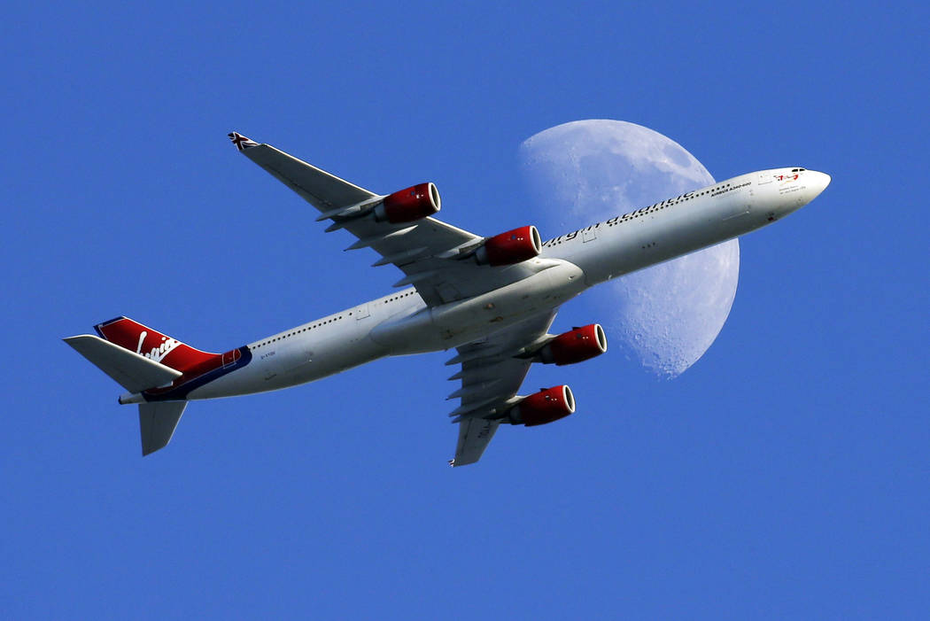A Virgin Atlantic passenger plane crosses a waxing gibbous moon Sunday, Aug. 23, 2015, on its way to the Los Angeles International Airport, in Whittier, Calif. Alaska said Wednesday, March 22, 201 ...